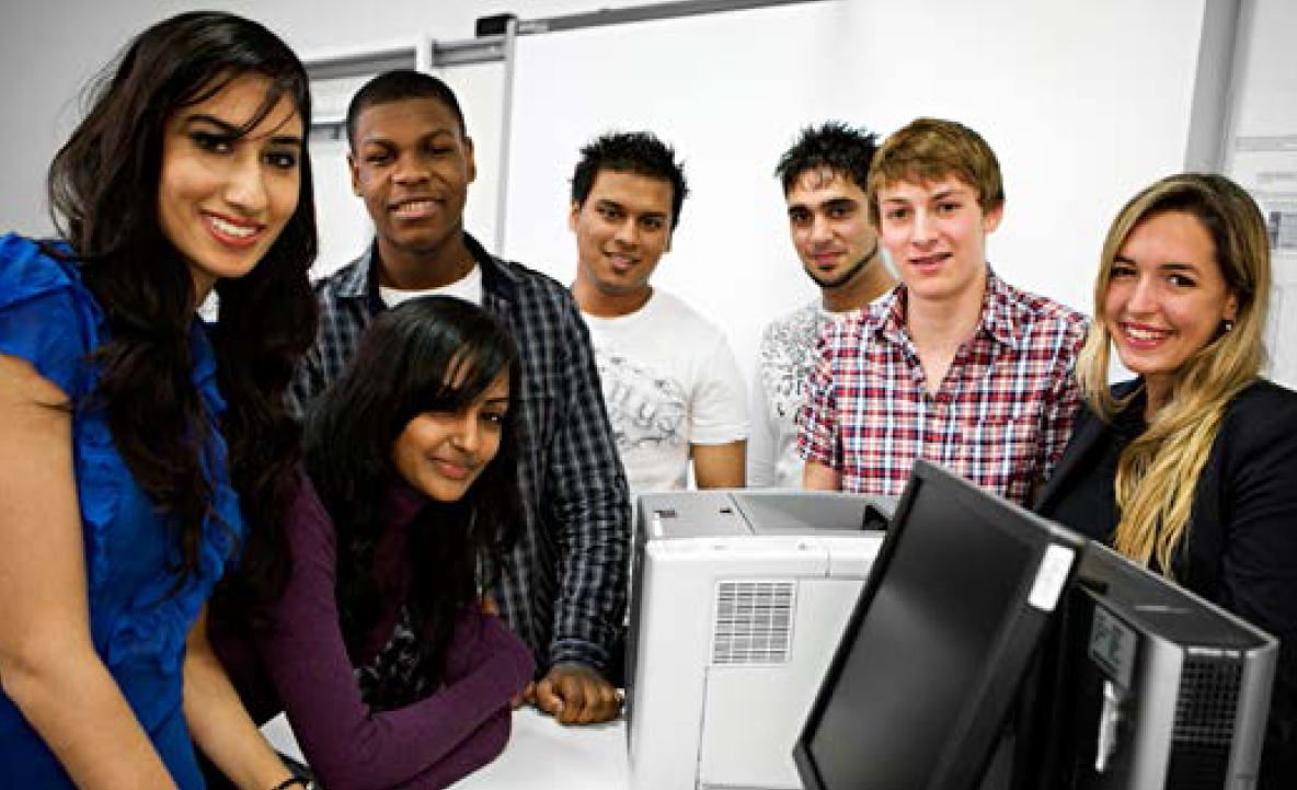 a group of smiling young women and men around computer, monitor, printer with a projector screen in the background